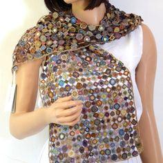 Une grande écharpe dans des tons brillants qui font ressembler la trame de cette écharpe crochetée main à des bijoux