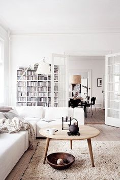 Homes: Danish: the living room with a coffee table and bookshelves in the background - Bookshelves, throws, a muted rug and the Hans Wegner coffee table. The white standing lamp is from Artemide.
