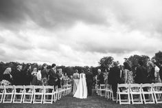 Walking down the isle. I love the sky in this photo - It rained all morning, cleared up right before the ceremony and stormed all night as we danced the night away.  Photography: Divine Light Photography - dlweddings.com