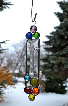 Emilys Rainbow Stained Glass Suncatcher measures approx 8 x 1.5 and has gems the color of the rainbow. It has a rectangular bevel to play with the light and wire detailing. It was my daughters design when she was home at Christmas. Something unique to add sparkle to your home. I include a suction cup for window hanging. Thank you for looking