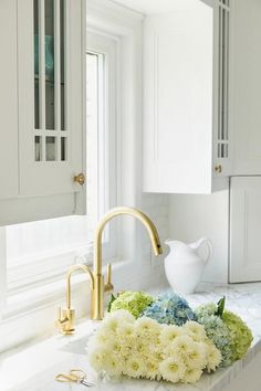 Brushed+gold+gooseneck+faucet+and+filter+paired+with+a+white+porcelain+sink+under+a+kitchen+window+flanking+glass-front+kitchen+cabinets+with+aqua+accents+inside.