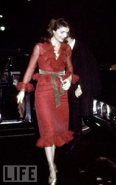 Onassis accessorizes a ruffled red dress with gold belt, bag, and shoes, arriving at La Cote Basque restaurant in 1970.