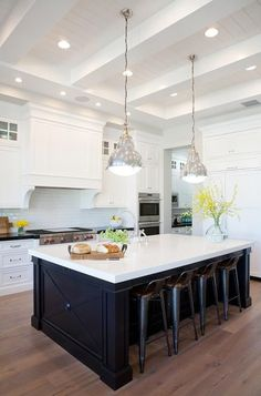 Charming white and black kitchen boasts two gorgeous Belmont pendants from Hudson Valley Lighting hung from a white beadboard and box beam ceiling over four black industrial counter stools sat in front of a black island topped with white quartz countertops fitted with a deck mount bridge gooseneck faucet positioned behind an island sink.