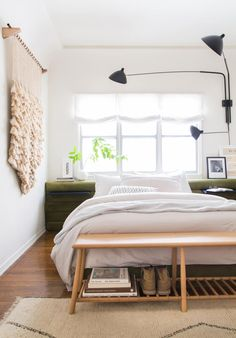 neutral colors, modern lines, lots of texture, pale rug, mid-century style bench, black sconce, woven art, green headboard