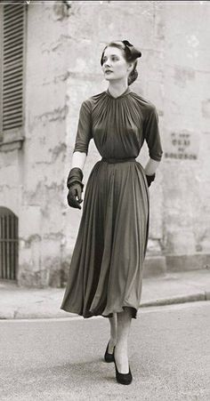 Model is wearing a light brown silk jersey dress by Grès and hat by Svend, photo by Jean Moral, Paris, 1954