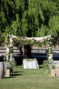 A verdant chuppah decorated with apples and roses | @mayamyersphoto | Brides.com