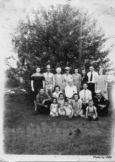 World War II Family 1942 or 1943. Vera Stout Anderson is third from left in back row, and Leonard Guy (Daddy Guy) Anderson is seated in the white shirt an no tie in the center. Their wartime family is gathered around. See story at Ancestors in Aprons. Killbuck, Ohio.