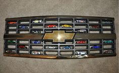 Displaying Hot Wheels in a Chevy grille. A cool place for all things miniture! Displaying Hot Wheels in a Chevy grille. A cool place for all things miniture! Car Part Furniture, Automotive Furniture, Automotive Decor, Furniture Design, Modern Furniture, Boys Furniture, Garage Furniture, Furniture Plans, Man Cave Garage