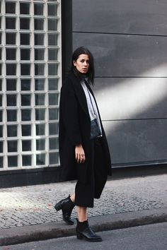 Lifestyleblog www.schwarzersamt.com is wearing a minimalistic autumn winter look with black culotte from Topshop, a Topshop sweater in light grey, a black coat from H&M and black high chelsea boots. The whole look is monochrome in black and grey.