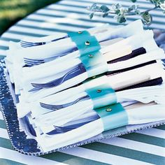 You'll need vellum strips (cut them from vellum sheets, found at paper supply stores) and brass beads. Punch the latter through the former, et voilà: chic wrappers for your napkins and flatware.  Cute idea for backyard wedding