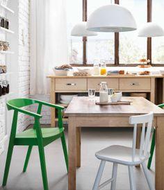 Uma cozinha com mesa e aparador em bétula maciça e cadeiras em verde e branco