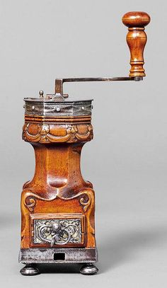 A TABLE TOP COFFEE MILL _ France, early 18th c. Fruitwood carved with garland, lion's heas and foliage. Cylindrical, tapering hopper on rectangular body with drawer for grinds, removable crank with wooden handle. The drawer front applied with brass sheating and openwork iron relief in the shape of a mascaron and foliage. H 28 cm. Screw clamp missing.