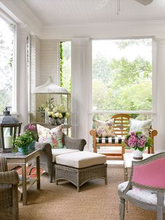 """Sunroom once a screened porch - She screened the existing side porch and opens doors that connect it to the living room. """"I suggest everyone find a way to have a porch. It really changes your lifestyle,"""" she says. Floral pillows and Lillian's """"Theodora"""" chair with a pink upholstered back contribute to the garden feel."""