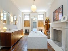 Julianne Moore's Bathroom - Julianne Moore converted the entire third floor of her townhouse to an enormous bathroom. This rectangular design features double vanity units, a modern bathtub and open fireplace.
