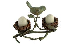 Egg-shaped ceramic salt and pepper shakers nest in this charming caddy made from recycled metal and natural vine, with a delightfully detailed cast-metal bird.