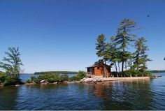"""Tuftonboro, NH -Here's a tiny home that comes with its own island on New Hampshire's Lake Winnipesaukee.Once owned by Bob Montana, the creator of the """"Archie"""" comic series, it's a one-room cedar cottage with a large, stone fireplace.  Size: 340 square feet"""