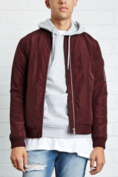 A woven padded bomber jacket with long sleeves, ribbed knit trim, a zippered front, a zippered sleeve pocket with three pencil holders, slanted front pockets, and an interior chest pocket.