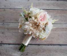 A soft and elegant silk bouquet with blush pink and ivory garden roses, dahlias, and peonies, accented with soft green lamb's ear. This wedding bouquet is wrapped in ivory satin, but can be customized