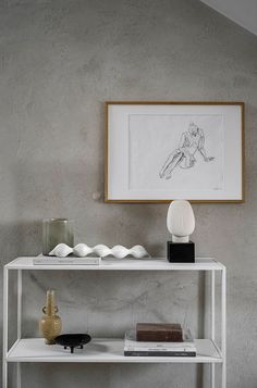 A white metal minimalist shelving unit styled with books and ceramics creates visual interest in this minimalist Scandi loft - limewashed walls - textured walls - styling shelves - line drawings - ceramics and vases in a Scandinavian home Nordic Living, Scandinavian Living, Minimalist Shelving, Open Plan Apartment, Metal Shelving Units, Concrete Coffee Table, Geometric Drawing, Art Walls, Nordic Interior