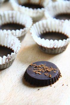Pirottini di carta con il cioccolato di carrube all'interno. In primo piano un cioccolatino con polvere di carruba in superficie.