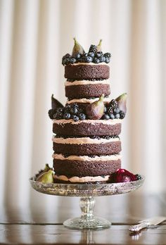Naked wedding cake featuring espresso-and-blackberry filling sandwiched between layers of chocolate cake. The dessert is topped off with fresh figs, blackberries, and blueberries.