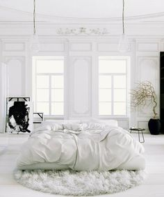 I like the white bed in the middle of the room. and the black vase with twigs