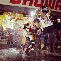 Marc Marquez being showered in champagne by his honda team after becoming 2014 world champion