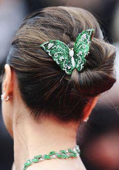 Una farfalla dalle ali ricamate si posa sui capelli raccolti dell'attrice Michelle Yeoh.