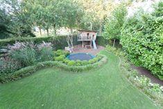 Dia 10 van 12: Als je kinderen hebt, is het een leuk idee om voor hen een ruimte in de tuin te creëren waar ze kunnen spelen. In deze tuin zien we een trampoline en een speelhuisje met glijbaan. En natuurlijk is er op het grasveld rondom de speelruimte ook nog genoeg plek om lekker te spelen. Wil je meer weten over het inrichten van een grote tuin? Lees dan ook dit artikel eens!