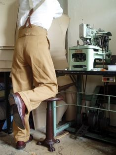 Tan medium weight drill high rise trousers. Popular, loose cut trouser style worn mainly but not exclusively by men. High back with braces buttons.