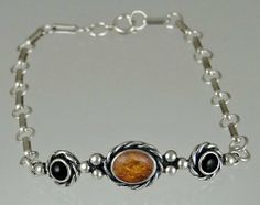 Sterling Silver Filigree Chain Bracelet with Genuine Amber Accented with Black Onyx The Silver Dragon- Bracelets. $63.00. This Bracelet Fits a Standard Woman's Wrist. Designed And Hand- Crafted in Sterling Silver. This Bracelet was Designed by The Silver Dragon, a Jewelry Shop in New England. Thank you for Supporting American Business.. The Silver Dragon uses Sterling Silver that has been Reclaimed... Helping Save Mother Earth's Resources.. This Unique Bracelet is Crea...