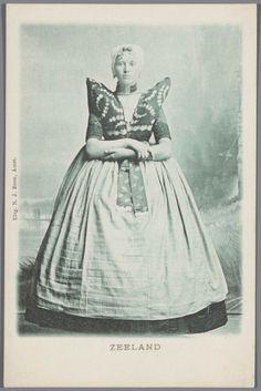 Vrouw in Axelse streekdracht. De vrouw draagt over de ondermuts en het oorijzer een 'trekmuts'. Ze draagt 'dubbele strikken' (dubbele, klaverbladvormige gouden oorijzerhangers) aan de 'krullen' (oorijzeruiteinden) van het oorijzer. Tussen de 'krullen' zijn twee gouden mutsenspelden in de muts gestoken. 1886-1905 #Zeeland #Axel