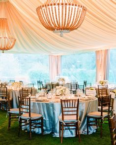 The clear plastic sides of the tent at Jessica and Andrew's wedding allowed guests to take in the beautiful scenery of Napa Valley, while the beaded wood chandeliers beneath draped fabric provided soft lighting from above.