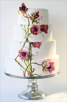 A four-tiered wedding cake features hand-painted flowers and vines, as well as pink sugar anemones.