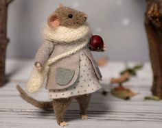 This little mouse was hand made by wool using needle felted techniques. It holds standing alone just have to adjust the foot and tail. The hands and the legs can be moved in different positions, also the head can be turned in both directions. It comes with a pink coat, gray skirt, pink scarf and Christmas twig in his hand. Tiny gift for you or a friend of yours, nice collectables woolen animal. Great present for everyone who admires handmade Eco-friendly creations.  Size is about 10 cm or…