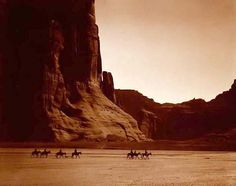 You are looking at a beautiful picture of Canon De Chelly. It was taken in 1904 by Edward S. Curtis.    The picture presents Seven riders on horseback and dog in trek against a background of canyon cliffs.