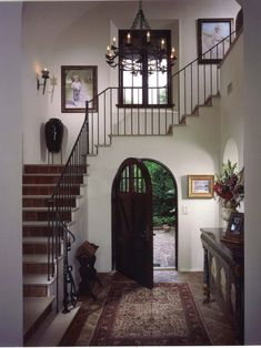 Entry Spanish Design - Spanish Revival interiors : 1) Decorative wrought iron. One prominent feature is the use of wrought iron throughout the home. This grand foyer accommodates a Spanish-style chandelier, wall sconces and stair railing.