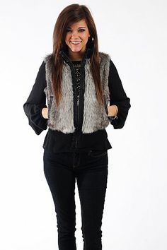"""Lucky Break Vest, Black $41.00  We love this fur vest! The gray fur is accentuated with black stretchy trim at the collar and hemline, and the zipper and pockets are trimmed with black leatherette. Put this on over your favorite top and jeans for a fabulous winter outfit!   Fits true to size. Miranda is wearing a small.   From shoulder to hem:  Small - 20""""  Medium - 21""""  Large - 22"""""""