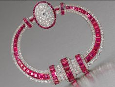A rare art deco ruby and diamond fibula brooch, by Georges Fouquet, circa 1925  Of tapering annular form, the central row of calibré-cut rubies within borders of old brilliant and single-cut diamonds, with three central vertical accents of similarly cut stones and completed by a diamond and ruby bombé cluster, signed G. Fouquet and numbered, maker's marks for Georges Fouquet in two places, French assay marks, diameter 6.8cm.