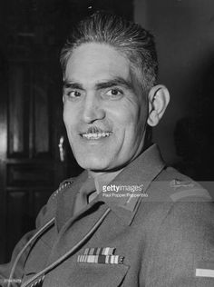 Portrait of Iraqi Prime Minister Abd al-Karim Qasim (Abdul Karim Kassem) (1914-1963) smiling as he sits at his desk at the Ministry of Defense, Baghdad, Iraq circa 1960.