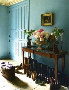 country house mud room - too many shoes (lol!) but I love the wall colour, flowers and picture frame