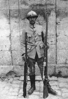 WW1. A French soldier carrying a German Mauser Tankgewehr 13 mm gun used in tank warfare and a standard issue French rifle. - Hulton Archive / Getty