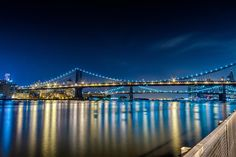 side view bridge at night with light reflections | Manhattan Bridge And Light Reflections In East River. Photograph