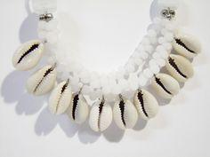 Colar em cabo de aço. Pingente confeccionado com miçangas brancas e búzios. Acabamentos em muranos, cerâmicas e contas em metal prateadas.