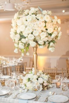 Tall gold centerpiece with white roses, cascading tulips, and gold leaves at base Dallas wedding