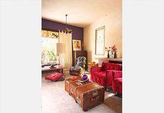 A mistura de elementos, como as poltronas vermelha e estampada, a parede roxa e a mala utilizada como mesa, faz desta sala um ambiente inspirador