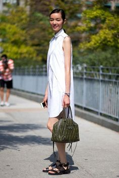 Model Fei Fei Sun wears a white shirtdress, strappy black sandals, and an olive green quilted Balenciaga bag