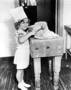 Cutie Shirley Temple is stuffing the turkey for her Thanksgiving feast.