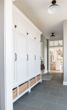 Home Remodeling Mudroom Blue and gray mudroom. Blue slate tile, white lockers and baskets in this lake house mudroom. - Gray and Blue Mudroom. Lake house mudroom feautring blue slate flooring, Boothbay Gray painted walls, and white lockers with baskets. Architecture Renovation, Home Renovation, Home Remodeling, Basement Renovations, Mudroom Laundry Room, Mud Room Lockers, Mudroom Cubbies, Mudroom Storage Ideas, Basement Storage