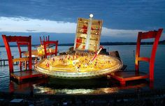 Singers perform on a giant stage, built up like a table and chairs from a Parisian bistro, in Lake Constance during a dress rehaersal of Giacomo Puccini's opera 'La Boheme' in 2002